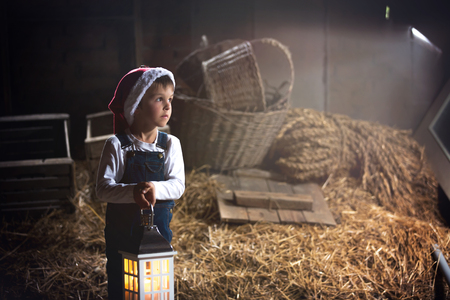 Sweet boy, holding lantern, looking through window, Christmas time in a barn