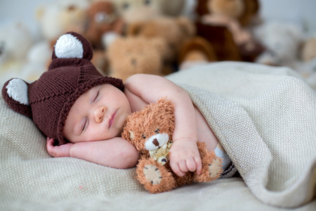 테 디 베어와 함께 침대에서 잠자는 작은 신생아 아기, 유아 장난감으로 쉬고 스톡 콘텐츠