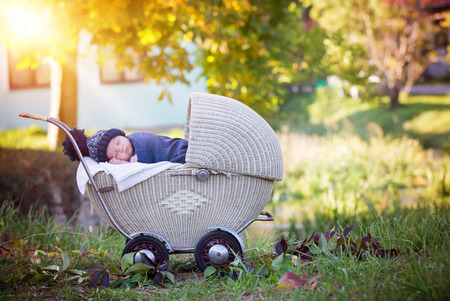 Little newborn baby boy, sleeping in old retro stroller in forest, autumn time, wrapped with scarf and knitted hat. Posed baby in retro pram, infant sleeping, vintage stroller