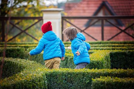 비가 오는 동안 공원에서 미로에서 행복하게 달려가는 두 자녀, 소년들. 스톡 콘텐츠