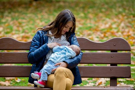Jeune maman, allaiter son bébé nouveau-né en plein air dans le parc, l'automne Banque d'images - 87903848