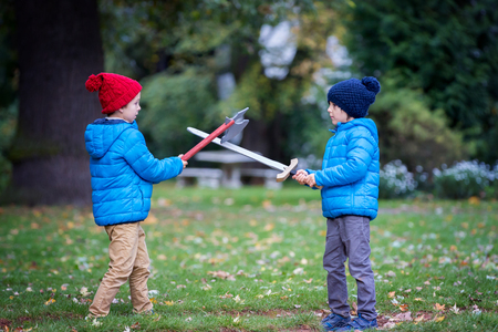Two boys, playing with swords in the park, autumn time Stock Photo