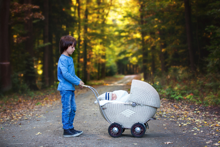 Sweet preschool boy pushing his little newborn baby boy, sleeping in old retro stroller in forest, autumn time, wrapped in scarf and knitted hat. Posed baby, retro pram, infant, vintage stroller