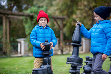 chessman: Two children, boy brothers, playing chess with huge figures in the park on the ground, autumn time. Childhood happiness concept, kids playing in the park fall time