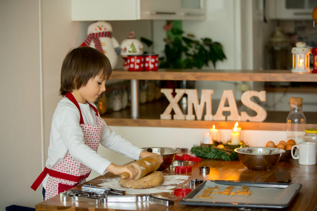 Two sweet children, boy brothers, preparing gingerbread cookies for Christmas, baking at home