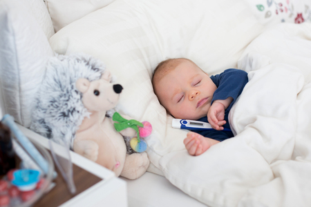 Cute newborn baby boy, lying in bed with cold and fever