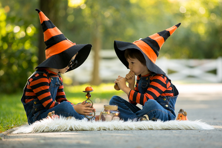 chandelier background: Two children, boy brothers in the park with Halloween costumes, having fun