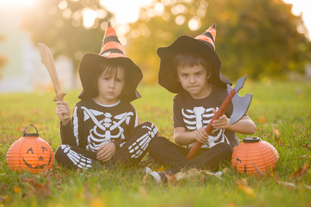 Two children, boy brothers in the park with Halloween costumes, having fun