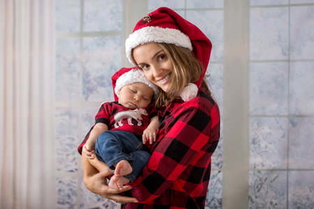 Young mother, holding her newborn baby boy, infant with santa hat. Family christmas portrait