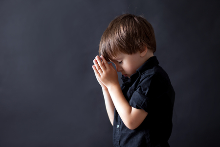 Little boy praying, child praying, isolated black background Stock Photo