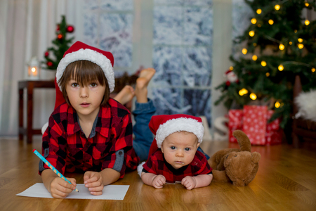 Cute newborn baby boy with Christmas hat, lying down on the floor, his older brother writing letter to Santa Claus