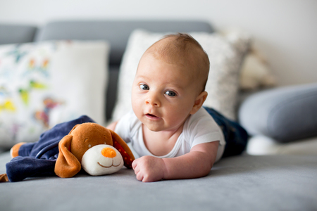 Adorable little baby boy, playing with toy, looking curiously at camera