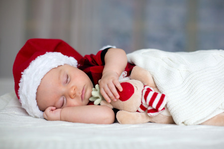 Little sleeping newborn baby boy, wearing Santa hat and jeans, holding toy Stock Photo