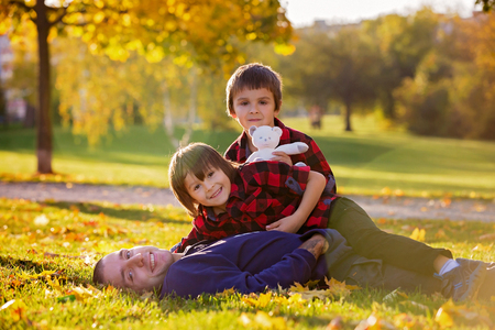 Cute funny children, playing with their father in the park, autumn time, nice afternoon back light Stock Photo