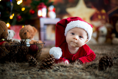 Portrait of newborn baby in Santa clothes in little baby bed, winter snow landscape outdoor