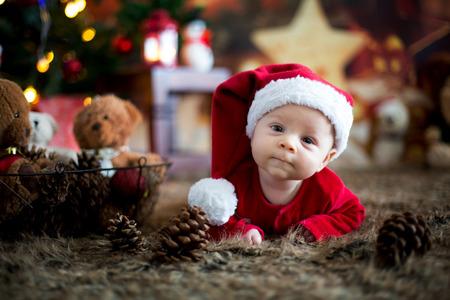 Retrato de bebé recién nacido en ropa de Papá Noel en la pequeña cama de bebé, paisaje de nieve de invierno al aire libre