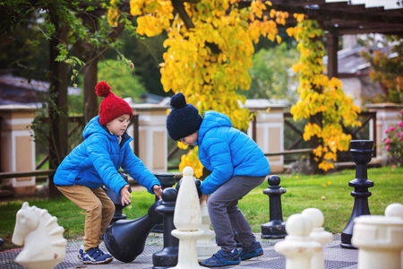 Two children, boy brothers, playing chess with huge figures in the park on the ground, autumn time. Childhood happiness concept, kids playing in the park fall time