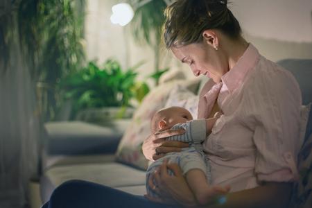 Young beautiful mother, breastfeeding her newborn baby boy at night, dim light. Mom breastfeeding infant