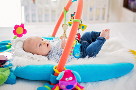 Cute baby boy on colorful gym, playing with hanging toys at home, baby activity and play center for early infant development. Kids playing at home 版權商用圖片