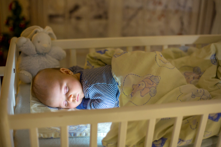 Adorable newborn baby boy, sleeping in crib at night. Little boy in blue striped pajamas taking a nap in dark room, christmas decoration in the room, winter time, snowing outdoors Zdjęcie Seryjne