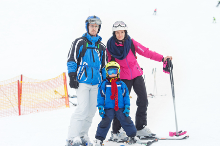 Young happy family with one child, skiing in the mountains, wintertime