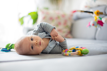 日当たりの良いリビングルームでおもちゃで遊ぶかわいい男の子、ソファに横たわって 写真素材 - 91808845