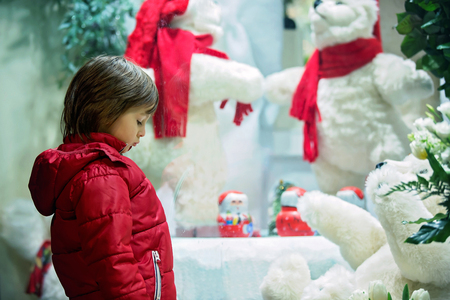 Sad little child, watching Christmas decoration with toys in a shop window display, wishing for a present Stock Photo