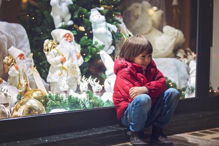 슬픈 어린 아이, 장난감을 가진 크리스마스 장식을 상점 창 디스플레이에보고, 현재를 바래 스톡 콘텐츠
