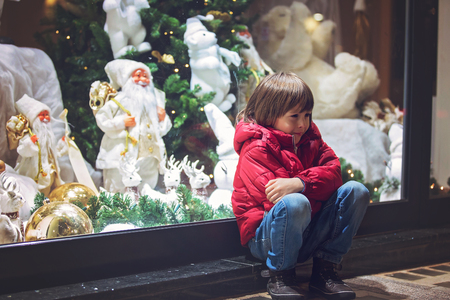 Sad little child, watching Christmas decoration with toys in a shop window display, wishing for a present Stok Fotoğraf - 94231096