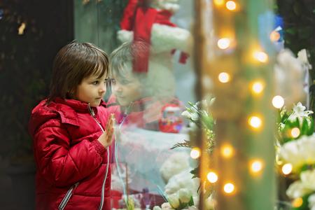 아름 다운 작은 아이, 소년, 상점 창 디스플레이에서 장난감을 가지고 크리스마스 장식을보고, 현재, 창에서 자신의 반사 소원 스톡 콘텐츠