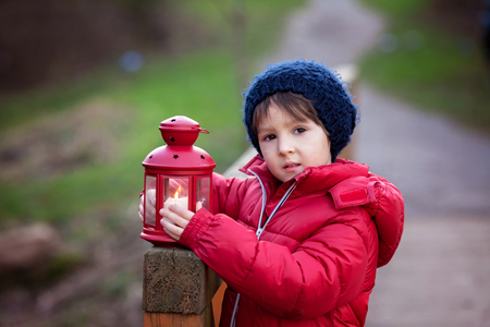 Sweet child, holding red lantern in the park on a sunny winter day, outdoors