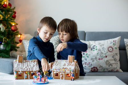 Two children, boy brothers, playing with gingerbread houses and little toys at home on Christmas Banque d'images