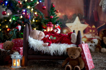 Portrait of newborn baby in Santa clothes in little baby bed, sleeping under Christmas tree, winter snow landscape outdoor