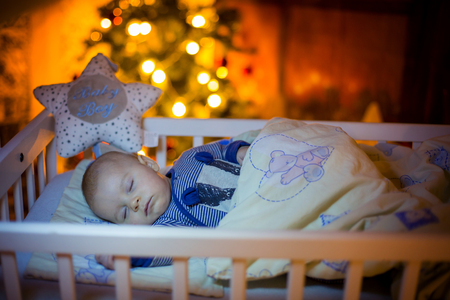Adorable newborn baby boy, sleeping in crib at night. Little boy in blue striped pajamas taking a nap in dark room, christmas decoration in the room, winter time, snowing outdoors Stock Photo