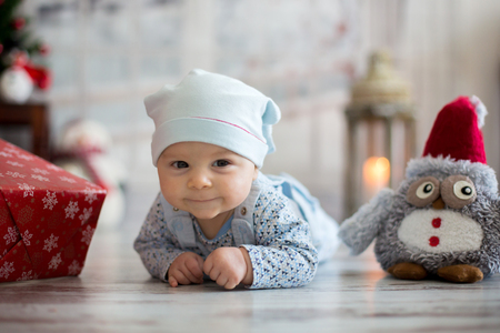 Cute christmas portrait of little baby boy, lying on his belly on the floor, smiling happily, christmas decoration and presents around him Stock Photo