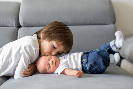 Sweet preschool boy, hugging with tenderness and care his little newborn brother at home Stock Photo