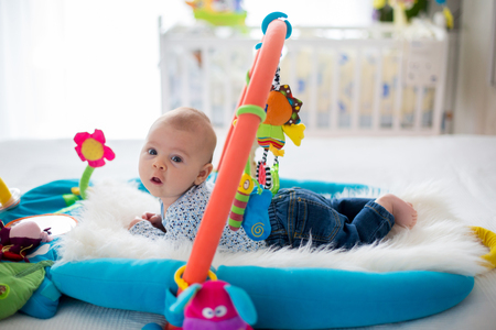 Cute baby boy on colorful gym, playing with hanging toys at home, baby activity and play center for early infant development. Kids playing at home Stock Photo