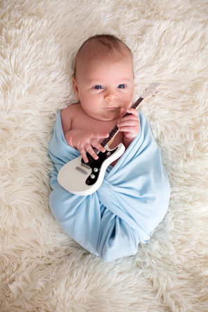 Newborn baby boy, wrapped in blue scarf, holding a little guitar and smiling Imagens