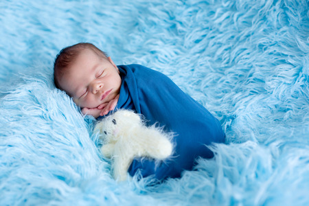 Cute baby boy, peacefully sleeping wrapped in blue wrap on a blue fur Stock Photo