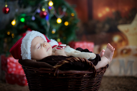 Cute three months old baby with bear hat in a basket, sleeping, christmas decoration around him