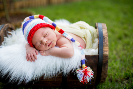 Little sweet newborn baby boy, sleeping in crate with knitted colorful hat in garden, outdoors in the park