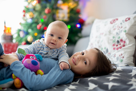 Six years old preschool boy, playing at home with his newborn baby brother, baby home activity. tenderness and care between siblings, family concept