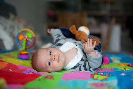 Gelukkig drie maanden oude babyjongen, thuis spelen op een kleurrijke activiteit deken, speelgoed en verschillende activiteiten om hem heen