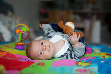 Happy three months old baby boy, playing at home on a colorful activity blanket, toys and different activity around him Stok Fotoğraf