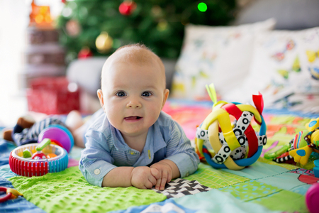 Happy three months old baby boy, playing at home on a colorful activity blanket, toys and different activity around him 写真素材
