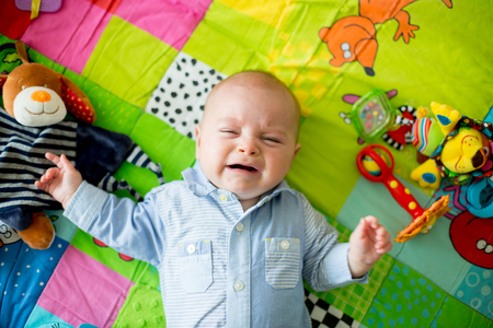 Three months old baby boy, crying at home on a colorful activity blanket, toys and different activity around him