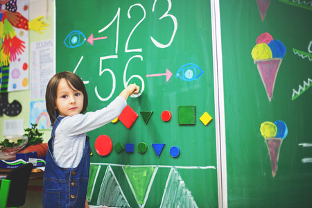 First grade boy at school, showing numbers and calculating in front of the blackboard Reklamní fotografie
