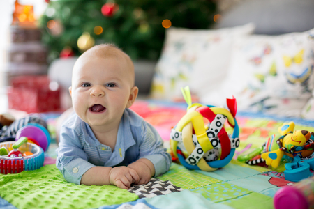 Happy three months old baby boy, playing at home on a colorful activity blanket, toys and different activity around him Stock Photo