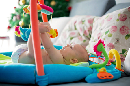 Little baby boy, playing with colorful toys at home, newborn baby activity, coordination and development