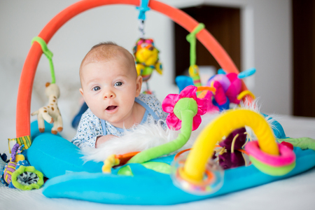 Cute baby boy on colorful gym, playing with hanging toys at home, baby activity and play center for early infant development. Kids playing at home Archivio Fotografico